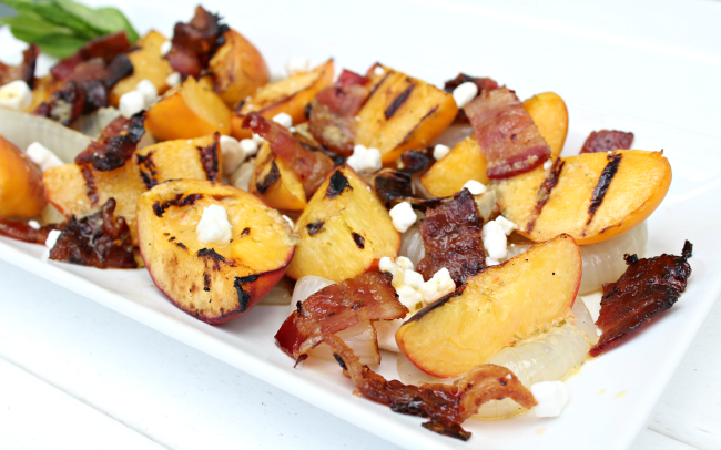 Fire up the grill and enjoy this Sweet & Salty Grilled Peach Salad with Bacon. This sweet and salty peach salad is balanced perfectly and topped with a fresh mint & peach vinaigrette dressing. Find the recipe on