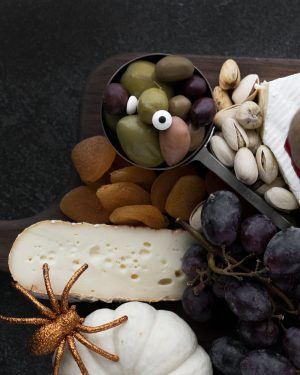 Looking for a creative way to entertain this Halloween? Check out these instructions on How to Create a Halloween Cheese Board. #cheeseboard #charcuterieboard #halloweencheeseboard #halloweenpartyideas #halloween #manthatlooksgood